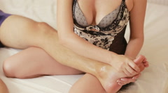 Girl in the bedroom makes a foot massage man. girl makes a relaxing foot massage Stock Footage