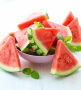 Triangular slices of watermelon with mint on white wooden background Stock Photos