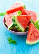 Triangular slices of watermelon with mint on blue wooden background Stock Photos