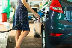 Woman fills petrol into the car at a gas station Kuvituskuvat