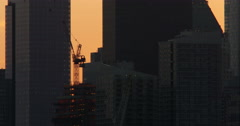 Construction crane silhouette among New York City skyscrapers during sunset Stock Footage