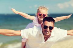 Happy family having fun on summer beach Stock Photos