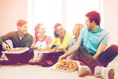 Five smiling teenagers eating pizza at home Stock Photos