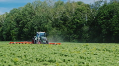 Tractor pulls on the field, agricultural mechanism for weeding plants. On a Stock Footage
