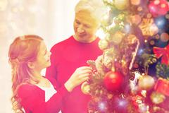 Smiling family decorating christmas tree at home Stock Photos