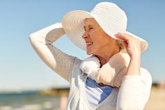 Happy senior woman in sun hat on summer beach Stock Photos