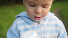 The beautiful child eats the ice cream Stock Footage