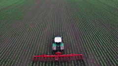 Tractor pulls on the field, agricultural mechanism for weeding plants. Side view Stock Footage