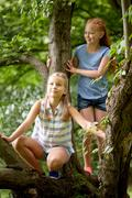 Two happy girls climbing up tree in summer park Stock Photos