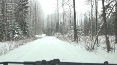 Driving on snow covered road in winter forest. Front car window view Stock Footage