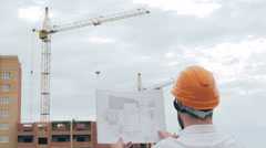 Chief architect at construction site. Chief architect in a hard hat at Stock Footage