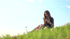 Pretty brunette girl in black leather dress using her smartphone on the lawn. 4K Stock Footage