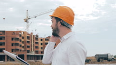 Architect talking on cell phone on a construction site Stock Footage