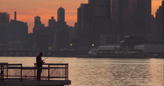 Man fishing on end of pier along Hudson River during sunset in New York City Stock Footage