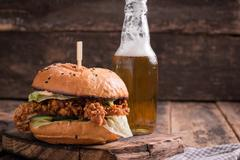 Fresh and tasty hamburger with a beer on a wooden table. Stock Photos