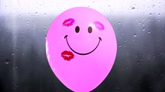 Pink Balloon with smiley and imprints of kissing lips at a rainy window bkg. Stock Footage