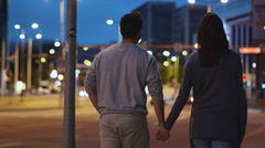Follow Shot of Attractive Happy Couple Walking on Streets of Night Town Stock Footage