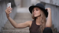 Pretty young girl in a black hat pictures of yourself on your smartphone Stock Footage