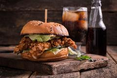 Fast food with burger or cheeseburger, and soft drink on vintage wooden table Stock Photos