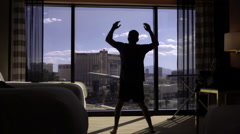 Man doing jumping jacks - silhouette of exercise in hotel room morning Las Vegas Stock Footage