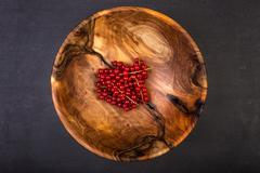Bunch of red currants in a bowl from walnut wood Stock Photos