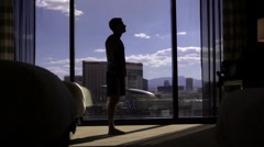 Silhouette of man doing Yoga in hotel room in slow motion, stretching Stock Footage
