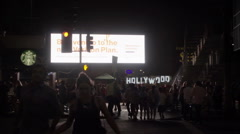 Couple walking, crossing street, Hollywood Boulevard with sign at night in LA Stock Footage
