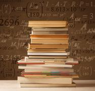 Books on vintage background with math formulas Stock Photos