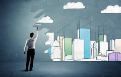 Salesman painting tall buildings on urban wall Stock Photos