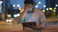 Attractive Man using Tablet Computer on Streets of Night Town. Stock Footage