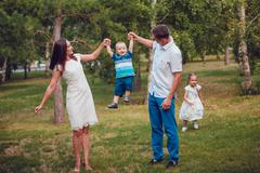 Young family of four having fun in the park Stock Photos