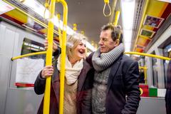 Senior couple standing in a crowded subway train Stock Photos
