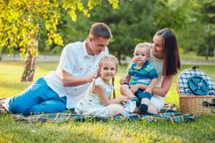 Young happy family of four on picnic in the park Stock Photos