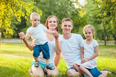 Young happy family of four sitting in the park on the grass Stock Photos