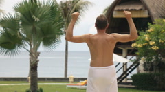 Excited man jumping in the exotic garden with sea view, super slow motion Stock Footage