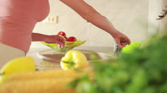 Girl washes grapes. vegetables on the kitchen table. tomatoes and cabbage Stock Footage
