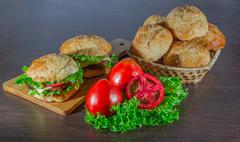 Sandwich - hamburger with burger, cheese, tomato, and onion on wooden background Stock Photos