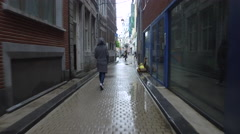 4K TRACKING shot of a young female walking in the street on a rainy day Stock Footage