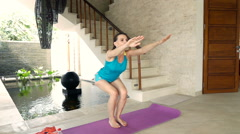 Young woman doing crouches on mat in luxury villa, super slow motion Stock Footage
