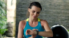 Young, happy, woman checking pulse on smartwatch after workout in luxury villa, Stock Footage