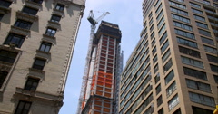 Construction crane slow moves rotates between New York City skyscrapers Stock Footage