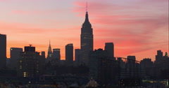 Iconic New York City skyline in front of orange and pink sky during sunset Stock Footage