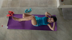 Young woman doing twist sit-ups on mat in luxury villa, top view, 240fps Stock Footage