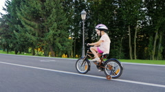 Steadicam shot: Funny girl five years old riding a bicycle with extra wheels Stock Footage