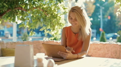 Young, attractive , girl sitting outdoors at a cafe using a tablet computer Stock Footage