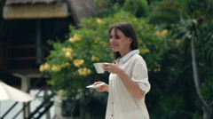 Happy woman walking with cup of tea in exotic garden and admire view, 240fps Stock Footage