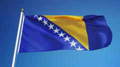 Bosnia and Herzegovina flag waving against clean blue sky, close up, isolated Stock Photos