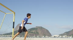 Soccer player scores a goal on the beach Stock Footage