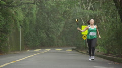 Slow motion female olympic torch runner Stock Footage