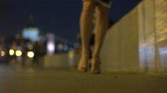 Blurred girl in high heels walking at the camera at night. Shallow focus 4K shot Stock Footage